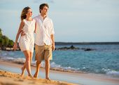 Romantic happy couple walking on beach at sunset. Smiling with arms around each other. Man and woman
