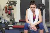 Tired and thoughtful young woman sitting in the gym