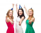 celebration, friends, bachelorette party, birthday concept - three smiling women wearing blue hats and showing thumbs up