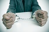a man wearing a suit sitting in a desk, with handcuffs in his wrists
