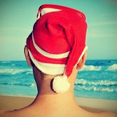 picture of someone on the beach wearing a Santa hat and a diving mask in his head, with a retro effect