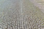 Old grey pavement of cobble stones in a circle pattern in an old medieval european town