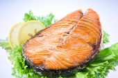 stock photo of salmon steak  - salmon steak with salad lettuce and lemon - JPG