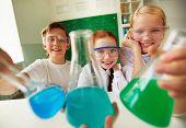 Drei glückliche Schulkinder holding Rohre mit chemischen Flüssigkeiten