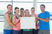 Portrait of a group of fitness class holding blank paper at a bright exercise room