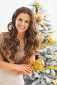 Portrait Of Smiling Young Woman In Front Of Christmas Tree