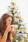 Happy Young Woman Drinking Latte Macchiato Near Christmas Tree