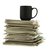 Coffee mug on top of stack of magazines