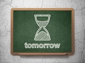 Time concept: Hourglass and Tomorrow on chalkboard background