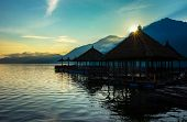 stock photo of chalet  - Peaceful village chalets on a volcano crater lake on Lake Batur - JPG