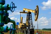 foto of nonrenewable  - Oilfield Pump Jack with a bright blue sky and clouds - JPG