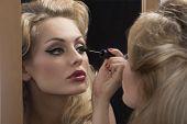 Aristocratic Girl Applying Mascara On Mirror