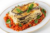 Vegetable lasagne, made with courgettes and eggplants (zucchini and aubergines), pasta sheets and bechamel sauce, served with a tomato and onion sauce and a basil garnish.