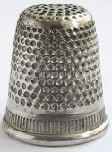 Close up a very old thimble white background.