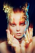 Art project: beautiful woman with golden make-up over black background. Jewelry, make-up. Fashion. L