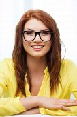 education, people and happiness concept - smiling teenage girl in eyeglasses at home