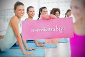 Fit blonde holding card saying membership against yoga class in gym