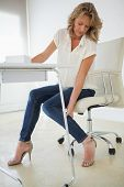 Casual businesswoman touching her ankle in her office