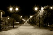 stock photo of pavestone  - night city lane with burning street lamps in sepia tone - JPG