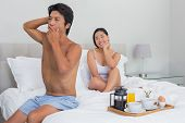 Smiling woman watching her boyfriend yawn and stretch at home in bedroom