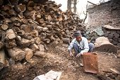 KATHMANDU, NEPAL - DEC 19, 2013: Unidentified a man sort wood for cremation rites in Bhasmeshvar Gha