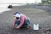 BALI - APRIL 11, 2014: A woman collects smoothen pebbles at the beach in Bali, Indonesia. Stones rou