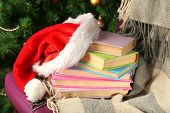 Composition with books and plaid, red hat, on chair on Christmas tree background