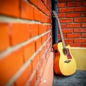 Guitar with red brick background.