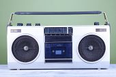 Retro cassette stereo recorder on table on green background