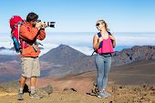 Photographer taking pictures of woman on hiking trip. Outdoor photography.