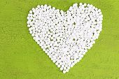Heart of pills on wooden background