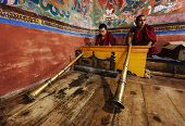 THIKSEY, INDIA - SEPTEMBER 4, 2011: Tibetan Buddhist monks with Tibetan horn (dungche) during prayer