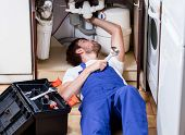 Man Repairing Pipes In The Kitchen