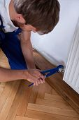 Man With Wrench Fixing Radiator