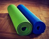 Vintage retro effect filtered hipster style image of Yoga mats on wooden floor