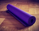 Vintage retro effect filtered hipster style image of Yoga mat on wooden floor
