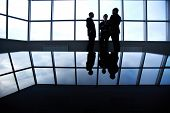 Three business partners having a discussion standing against a panoramic window in office