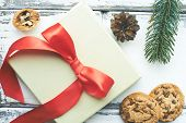 Composition of biscuits, walnut, pine cone, conifer and xmas card with red bow