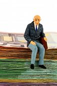 symbol photo for retirement and old age, figure of an old man sitting on a stack of bills