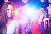 Attractive girl posing on dance-floor in nightclub