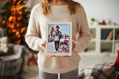 Girl in white knitted sweater showing image of beloved man with her portrait in touchpad