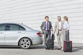 Businesspeople with luggage discussing outside car on street
