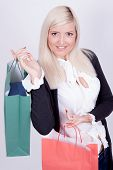 Portrait Of A Blond Woman With Shopping Bags In A Studio