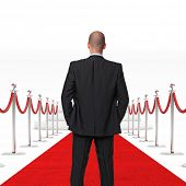 standing businessman and red carpet