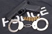 stock photo of snitch  - police concept with gun ammo and handcuffs - JPG