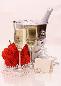 Two Champagne Glasses, Red Roses. Golden Wedding Rings