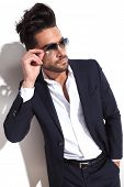 angle view of a handsome business man putting on his sunglasses with one hand in his pocket, looking away from the camera