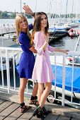Two Fashionable Girls Resting At A Marina.