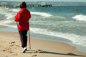 Nordic Walking. Woman Hiking On The Beach.