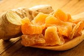 image of home remedy  - Closeup dried candied crystallized ginger pieces and fresh root on wooden table - JPG